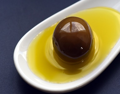Wer Olivenöl kaufen möchte, sollte sich auch mit der Herstellung und den Qualitätsunterschieden auseinandersetzen. Die Herstellung von Olivenöl beginnt mit der Ernte, welche idealerweise zwischen Oktober und Februar stattfindet, zu dem Zeitpunkt, wenn die Olive langsam ihre Farbe von grün zu violett wechselt. Oliven in bergigen Gebieten werden von Hand gepflügt, wohingegen in ebenen Gegenden vorwiegend Maschinen zur Ernte eingesetzt werden. Bei der Ernte dürfen die Oliven nicht beschädigt werden. Dies hätte erheblichen Einfluss auf die Qualität des Olivenöls. Um eine optimale Qualität zu gewährleisten, sollte spätestens drei Tage nach der Ernte die Pressung stattfinden. Traditionelle Pressmethoden Die traditionelle Pressmethode zeichnet sich dadurch aus, dass die Oliven von Ästen und Zweigen gesäubert und anschließend gewaschen werden. Danach werden sie, samt Kerne, von Mühlensteinen zu einem Brei verarbeitet. Dieser Brei wird anschließen in einer hydraulischen Presse ausgepresst. Diese Mischung aus Fruchtwasser und Öl wird in einer Zentrifuge voneinander getrennt und schließlich gefiltert. Moderne Pressmethoden Bei modernen Pressmethoden kommen Maschinen zum Einsatz, die abgesehen von einer schnelleren Verarbeitung auch einen höheren Ertrag bieten. Zuerst werden die zu verarbeitenden Oliven mehrere Stunden in luftdurchlässigen Containern gelagert, um schließlich per Förderband zur Absauganlage transportiert zu werden, wo die Äste und Zweige abgesaugt werden. Nach dem Waschen, werden die Oliven zerkleinert und anschließend wird der Brei 20 Minuten gerührt. Durch Schläuche wird der Brei in einen Dekanter transportiert, wo eine erste Trennung von Fruchtwasser und Öl stattfindet. Später wird in der Zentrifuge eine erneute Trennung durchgeführt, die sicherstellt, dass es sich bei dem Ergebnis um reines Olivenöl handelt. Geschmacksrichtungen Die Geschmacksrichtung des Olivenöls hängt in erster Linie von dem Zeitpunkt der Ernte ab. Früh geerntete Oliven ergeben einen kräf